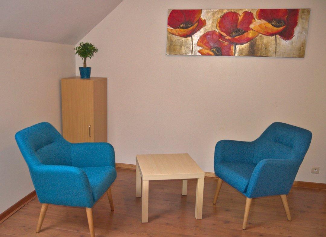 """Praktijkkamer """"Ooh mama toch!"""" met blauwe fauteuils, tafel en schilderij"""